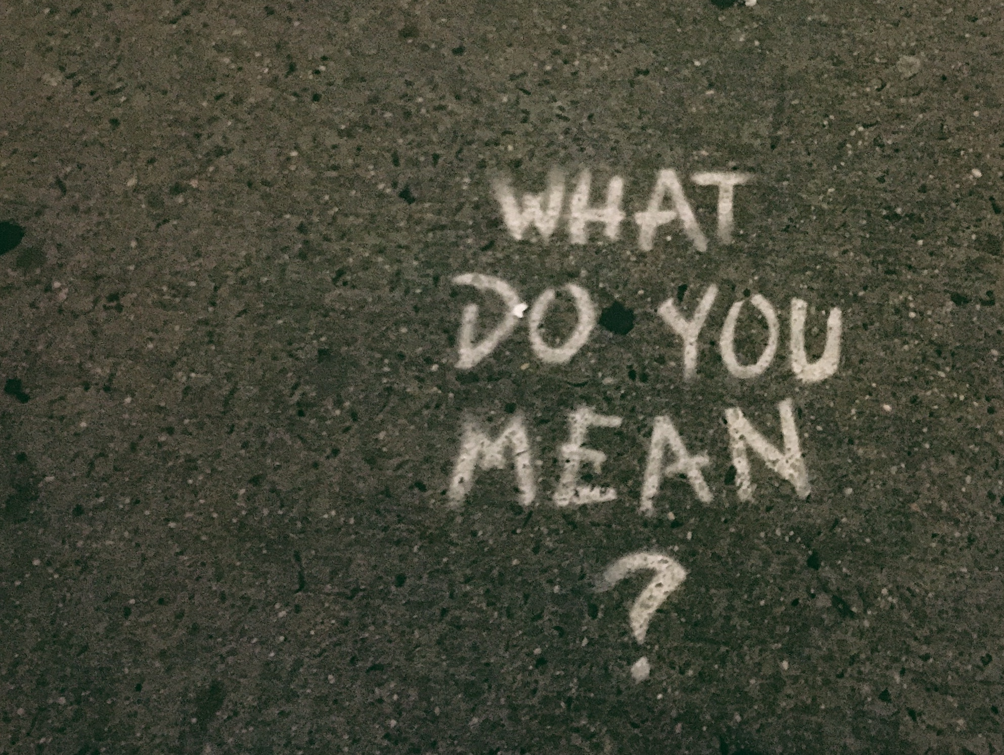 "Pavement with ""What do you mean?"" spray-painted on in white paint"
