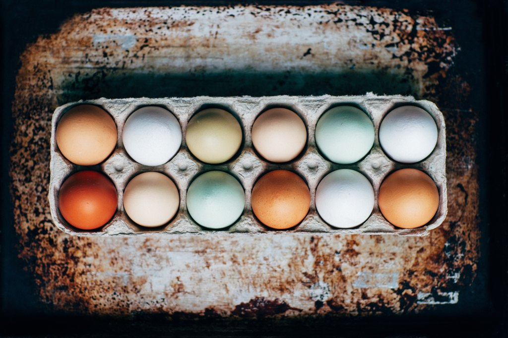 Multi-colored eggs in a carton, on a rusted tray.